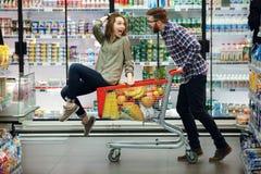 Pares bonitos que têm o divertimento ao escolher o alimento no supermercado fotografia de stock