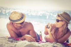 Pares bonitos que tacheiam fotos na praia imagens de stock