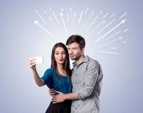 Pares bonitos que tomam o selfie com setas Fotos de Stock