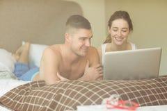 Pares bonitos usando o portátil na cama fotos de stock