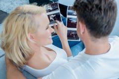 Pares brancos no sofá que olha imagens junto Imagens de Stock