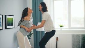 Pares brincalhão dos estudantes que têm o divertimento em casa que dança na cama no quarto filme