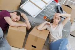 Pares cansados que descansan en nuevo hogar durante la mudanza fotografía de archivo libre de regalías