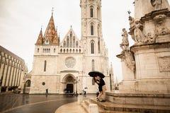 Pares cariñosos abrazados por el bastión del pescador en Budapest, Hungría en un día lluvioso fotos de archivo