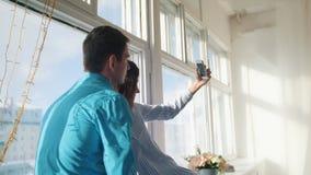 Pares cariñosos alegres felices que hacen el selfie en ventana, individuo atractivo joven y muchacha almacen de metraje de vídeo