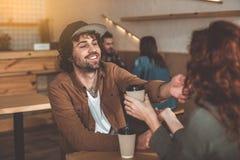 Pares cariñosos alegres que tienen fecha en cafetería Fotografía de archivo libre de regalías