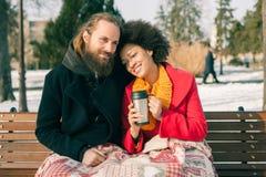Pares cariñosos con las bebidas calientes que se sientan en banco en invierno Fotos de archivo libres de regalías