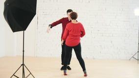 Pares cariñosos de la familia en camisas rojas - la hembra y el varón está bailando juntos en estudio almacen de video