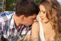 Pares cariñosos de los individuos y de las muchachas que mienten en la hierba en el prado, hombre que besa a una muchacha en el h Foto de archivo