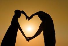 Pares cariñosos de Sillhouette en la puesta del sol con el corazón Imagen de archivo libre de regalías