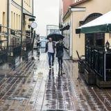 Pares cariñosos debajo de un paraguas que camina abajo de la calle de la ciudad vieja Fotos de archivo libres de regalías