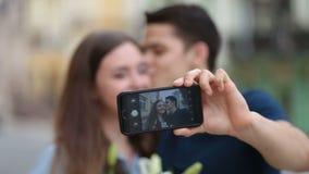 Pares cariñosos el día de fiesta que hace el selfie en el teléfono metrajes