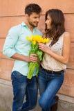 Pares cariñosos El donante del hombre florece a su novia imagen de archivo libre de regalías