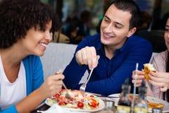 Pares cariñosos en almuerzo con los amigos Imagen de archivo