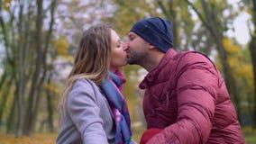 Pares cariñosos en beso blando en parque del otoño almacen de metraje de vídeo
