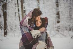 Pares cariñosos en bosque nevoso del invierno Foto de archivo