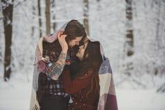 Pares cariñosos en bosque nevoso del invierno Fotos de archivo