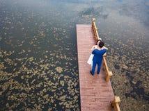 Pares cariñosos en el muelle en el lago foto de archivo