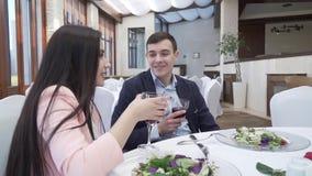 Pares cariñosos en el restaurante que bebe el vino rojo en el vídeo de la cantidad de la acción de la cena metrajes