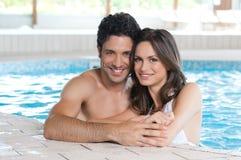 Pares cariñosos en la piscina del balneario foto de archivo
