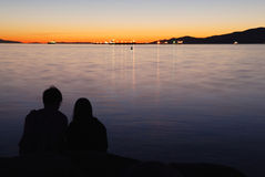Pares cariñosos en puesta del sol Fotografía de archivo