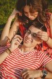 Pares cariñosos felices con los auriculares que escuchan la música de un smartphone y que abrazan al aire libre verano Fotografía de archivo libre de regalías