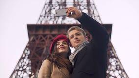 Pares cariñosos felices de los turistas que hacen el selfie en el fondo de la torre Eiffel almacen de video