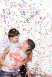 Pares cariñosos felices en confeti Foto de archivo