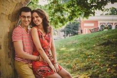 Pares cariñosos felices hermosos en ropa roja en la naturaleza bajo abarcamiento grande del árbol Fotografía de archivo libre de regalías