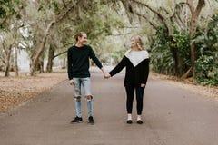 Pares cariñosos felices jovenes lindos que caminan abajo de un camino abandonado viejo con sobresalir por cubierto de musgo de l foto de archivo libre de regalías