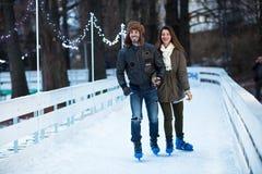 Pares cariñosos felices jovenes que patinan en la pista de hielo al aire libre Fotos de archivo