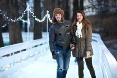 Pares cariñosos felices jovenes que patinan en la pista de hielo al aire libre Fotografía de archivo