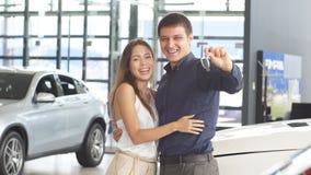 Pares cariñosos felices que abrazan cerca de su nuevo coche de lujo en la representación almacen de metraje de vídeo