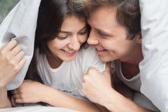 Pares cariñosos felices que disfrutan del momento romántico debajo de la manta foto de archivo
