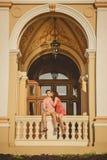 Pares cariñosos felices que se besan y que se sientan afuera en el balcón de Odessa Opera House Foto de archivo libre de regalías