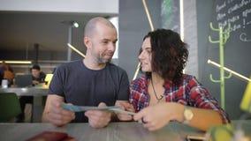 Pares cariñosos felices que se sientan en la tabla en cafetería y que miran sus boletos El hombre joven y la mujer sonrientes son metrajes