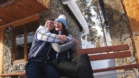 Pares cariñosos felices que se sientan en un banco cerca del chalet del invierno en las montañas almacen de video