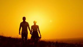 Pares cariñosos - hombre joven y muchacha hermosa que caminan en el prado de la puesta del sol - silueta, a cámara lenta almacen de video