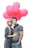 Pares cariñosos jovenes con los globos rojos Imagen de archivo libre de regalías