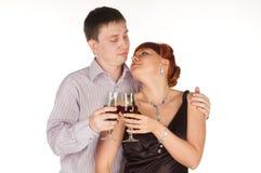 Pares cariñosos jovenes con los vidrios de vino rojo en manos Foto de archivo libre de regalías