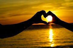 Pares cariñosos jovenes el día de boda en la playa tropical y la puesta del sol Foto de archivo