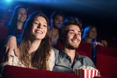 Pares cariñosos jovenes en el cine Imágenes de archivo libres de regalías