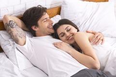Pares cariñosos jovenes felices que se relajan en cama imagenes de archivo