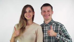 Pares cariñosos jovenes felices que sonríen a la cámara, mostrando los pulgares para arriba metrajes