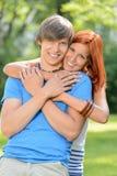 Pares cariñosos jovenes que abrazan en parque soleado Fotos de archivo libres de regalías
