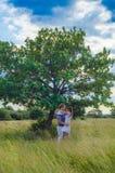 Pares cariñosos jovenes que se abrazan en el campo cerca de un tr Foto de archivo