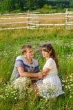 Pares cariñosos jovenes que se abrazan que se sienta en la hierba Imagen de archivo