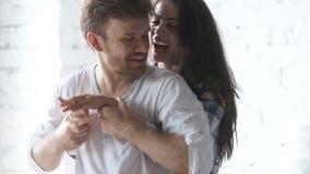 Pares cariñosos jovenes cariñosos que se divierten que abraza el abrazo en casa metrajes