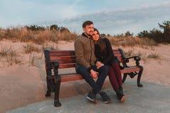 Pares cariñosos jovenes que se sientan en bancos cerca de la orilla de mar en otoño Imagenes de archivo