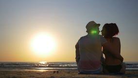 Pares cariñosos jovenes que se sientan en la playa y besarse metrajes